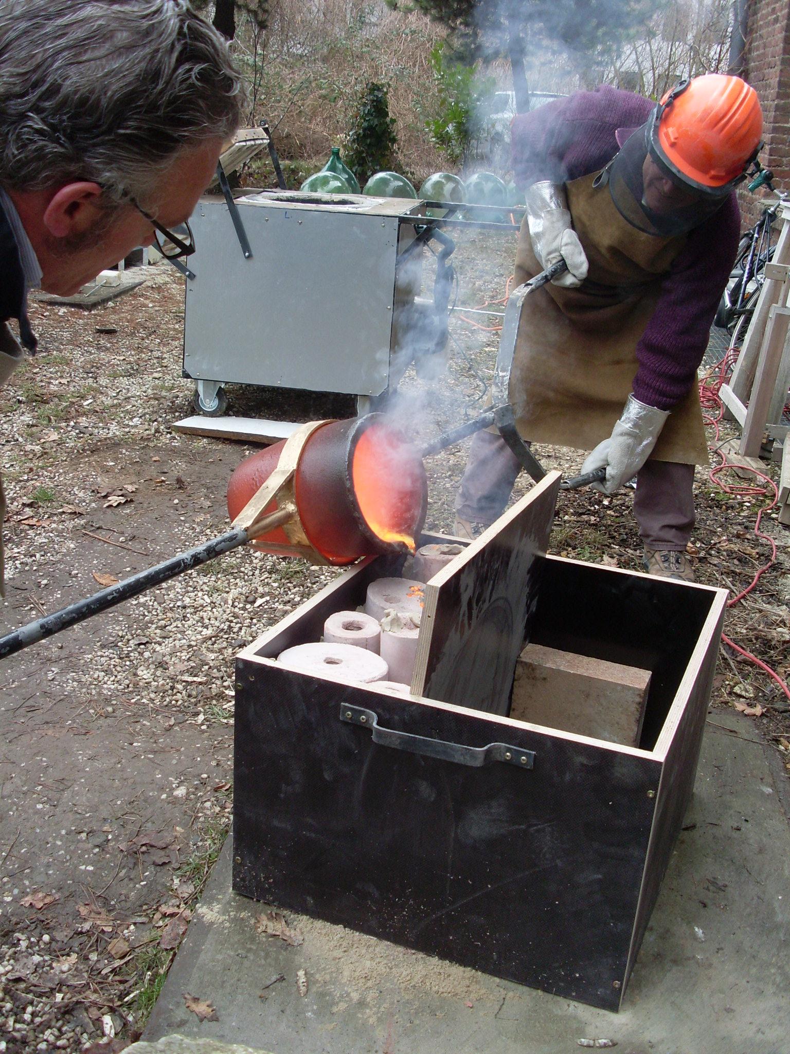 Einfüllen der geschmolzenen Bronze während des Gießvorganges